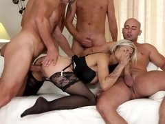 A blonde is taking on several men at the same time in a gangbang