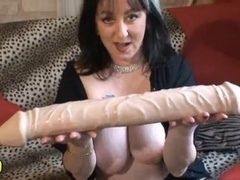 Une femme joue avec un gros Gode