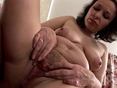 A brunette granny is getting ready to masturbate in closeup with her toys