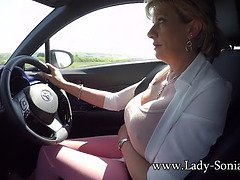 Mature blond Lady Sonia plays with her tits while driving